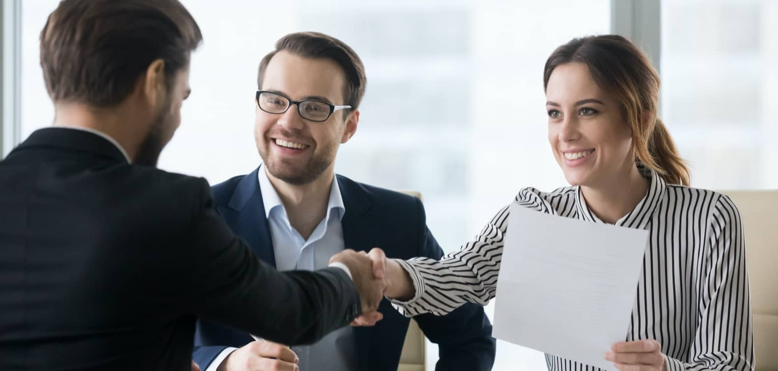 SME owner shakes hands with smiling female investor